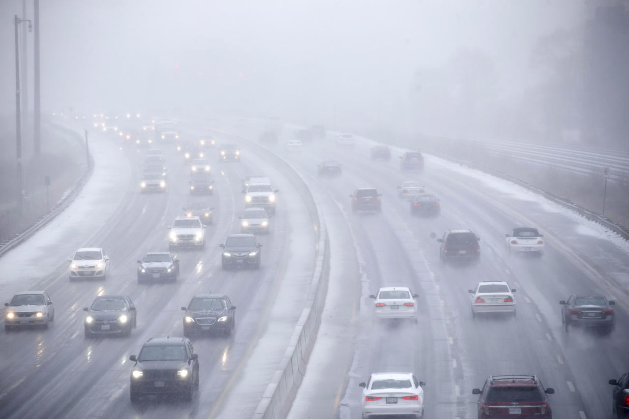 <p>Cars drive along Toronto's Lakeshore Drive as visibility diminishes through falling hail, snow, and rain in Toronto, Ont. on Saturday, April 14, 2018. (Photo from The Canadian Press/Cole Burston) </p>