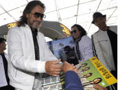 """Members of the Mexican grupera band Los Bukis Marco Antonio Solis signs an album as Jose Javier Solis, center and Eusebio """"El Chivo"""" Cortez, right, look on at press conference at SoFi Stadium on Monday, June 14, 2021, in Inglewood, Calif. Twenty five years after their last show as a band, the group announced that they are reuniting for a U.S. tour. (AP Photo/Chris Pizzello)"""