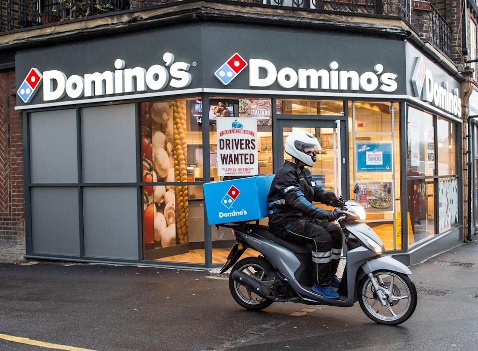 <p>A delivery rider outside a branch of Domino's Pizza</p> (PA Media)