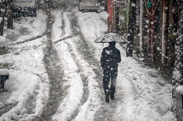 2019/11/09: A resident walks along a snow covered road while holding an umbrella during the heavy snowfall in Kashmir.