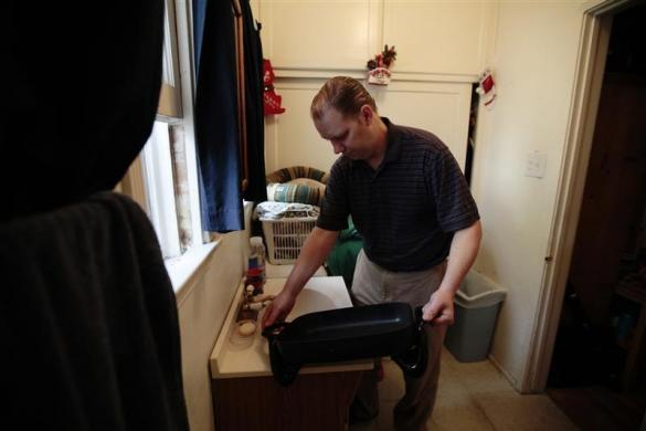 Tracy Burger, 45, washes dishes in a bathroom sink in a converted garage in Los Angeles, California December 18, 2011. Tracy and his wife Elizabeth, 43, lost their apartment in 2009 after both losing their jobs with combined earnings of $100,000 a year. They were forced to sell most of their possessions and live in a motel before moving into Elizabeth's mother's garage with their son Dylan, 8, in March 2011.