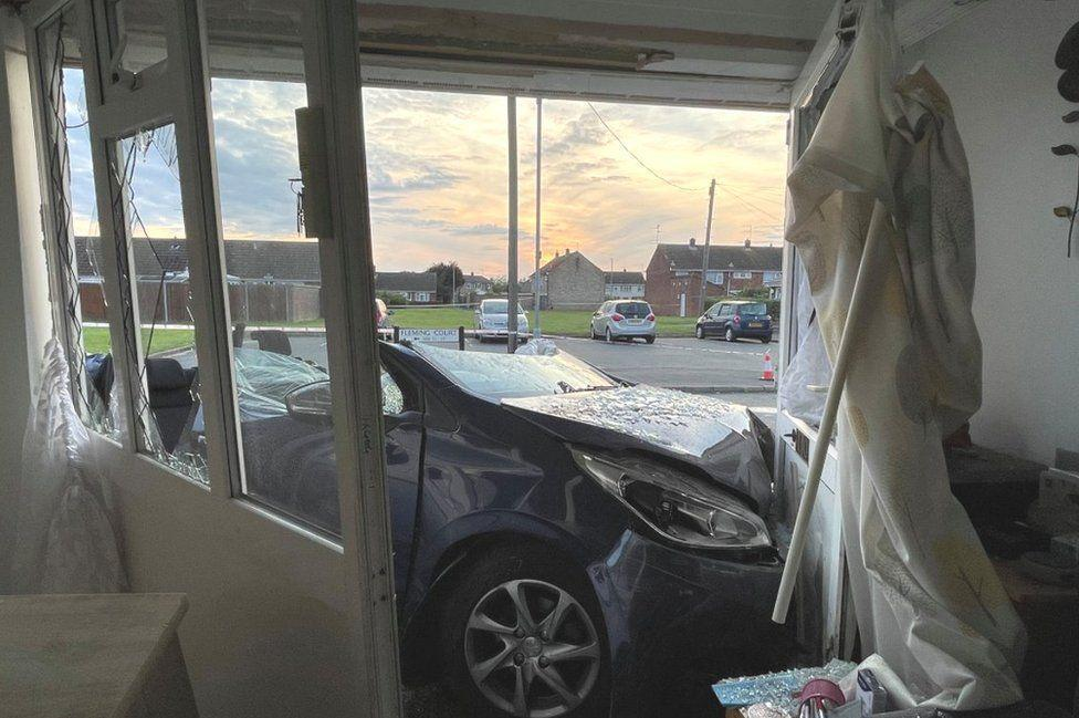 The homeowner was watching TV when the car crashed through her home. (Police)