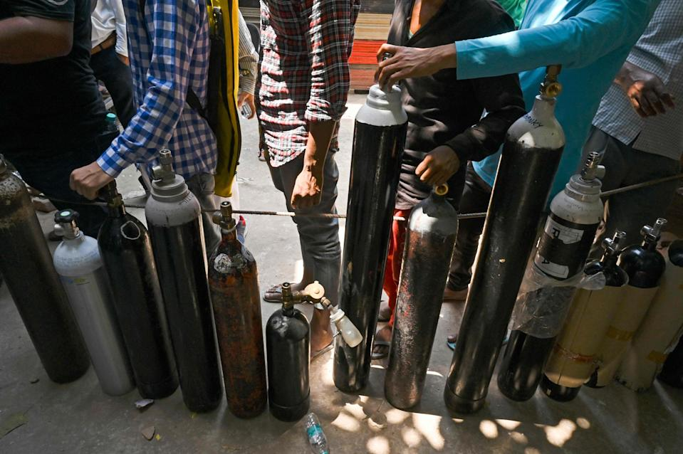 <p>People wait in a line to refill oxygen cylinders for Covid-19 coronavirus patients at a refilling centre in New Delhi on Wednesday</p> (AFP via Getty Images)