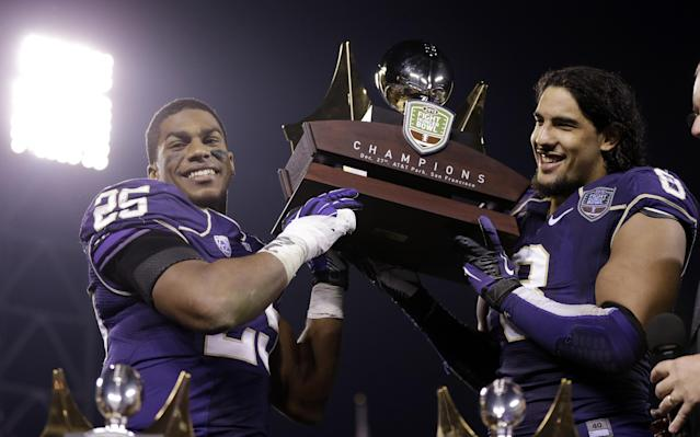 Washington running back Bishop Sankey, left, and defensive end Hau'oli Kikaha hold the winner's trophy after a 31-16 win over BYU during the Fight Hunger Bowl NCAA college football game on Friday, Dec. 27, 2013, in San Francisco. (AP Photo/Marcio Jose Sanchez)