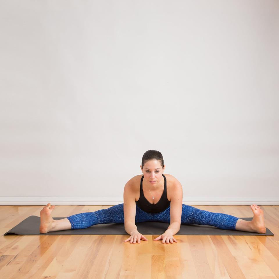 <ul> <li>Sit down with your feet about three to four feet apart (not as wide as you can go). Reach back with your right hand and move the flesh of your right bum cheek away from you, then do the same with your left. This will help your pelvis ground more firmly so you can stretch your hamstrings more effectively.</li> <li>Sit tall, reaching your head away from your hips, and draw your belly and ribs in. Keep that length as you begin to fold forward at your waist, sliding your hands down your legs or on the floor in front of your head.</li> <li>Go down as far as you need to feel a stretch in your hamstrings, but you don't want to feel pain.</li> <li>Hold here for five breaths. Then walk your hands over to your right leg, hold for another five breaths, and then repeat over the left leg.</li> </ul>