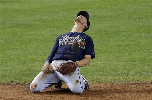 Atlanta Braves' Andrelton Simmons reacts to missing a ground ball for a base hit by Arizona Diamondbacks' Gerardo Parra during the fifth inning of a baseball game, Wednesday, May 15, 2013, in Phoenix. (AP Photo/Matt York)