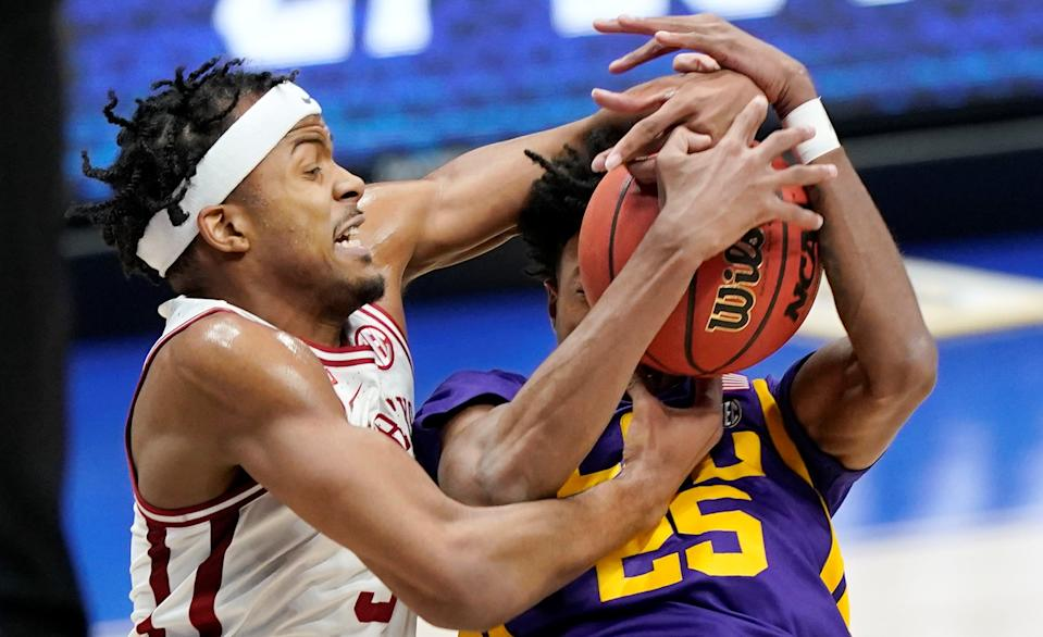 Arkansas' Moses Moody (left) and LSU's Eric Gaines (25) fight for a rebound in the first half of an NCAA college basketball game in the Southeastern Conference Tournament.