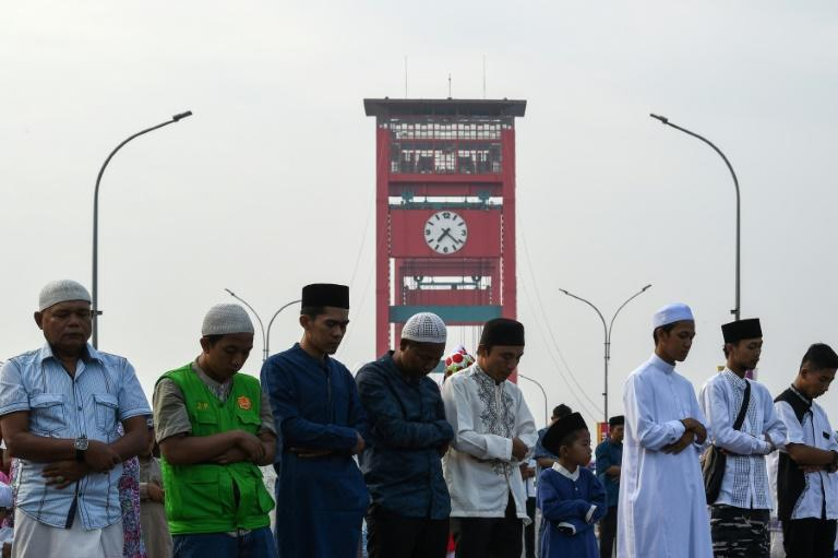 Indonesian Muslims offer Eid al-Adha prayers on Ampera bridge in Palembang, one of the host cities of the Asian Games