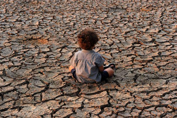 PHOTO: A child sits in at an area affected by a drought on Earth Day in the southern outskirts of Tegucigalpa, Honduras on April 22, 2016. (Orlando Sierra/AFP via Getty Images)