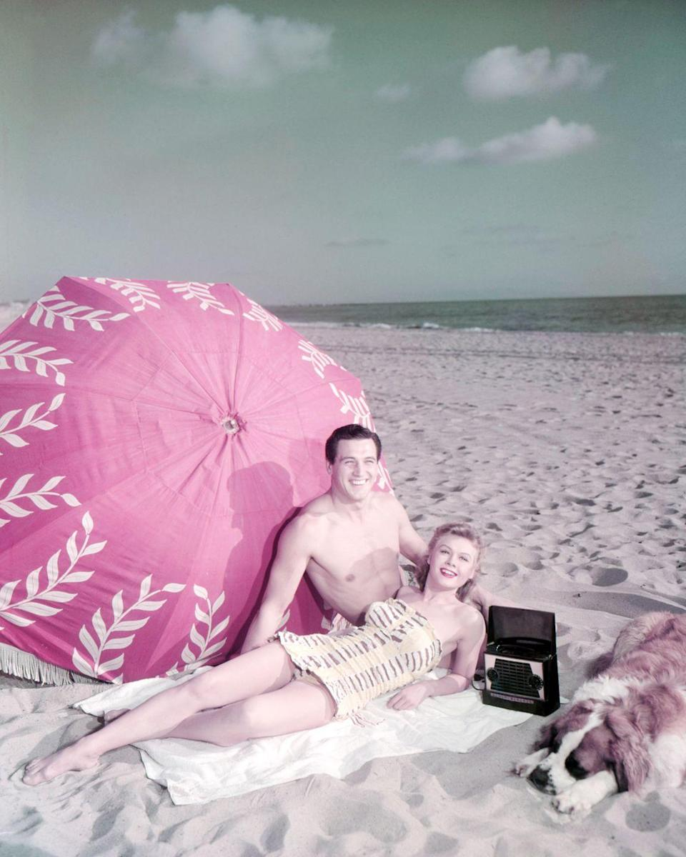 <p>Rock Hudson and Vera-Ellen enjoy the dog days of summer while lounging on a beach towel, circa 1955.</p>