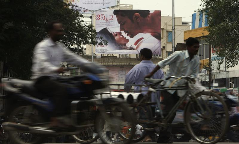 """Indian commuters move past a poster of Bollywood film """"Jism 2"""" in Hyderabad, India, Thursday, Aug. 2, 2012. """"Jism 2"""" stars a hard-core porn actress, and it does have that pesky title. But it's not a porn movie. Bollywood is certainly not ready for that. The film, which will be released across India on Friday, is pushing the ever-widening sexual boundaries enjoyed by many in urban India. (AP Photo/Mahesh Kumar A.)"""
