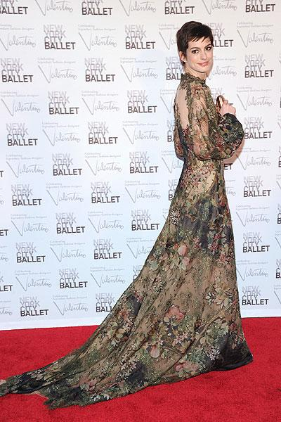 """Anne Hathaway looks stunning on the red carpet at New York City Ballet's fall gala on Sept. 20, 2012, in a sheer floral Valentino showstopper. The """"Dark Knight Rises"""" actress' cute pixie haircut juxtaposes the voluminous gown which features a print inpsired by the impressionist period. Although the dress is sheer, it's still elegant and modest, with the flowers covering her up. (Photo by Jamie McCarthy/Getty Images)"""