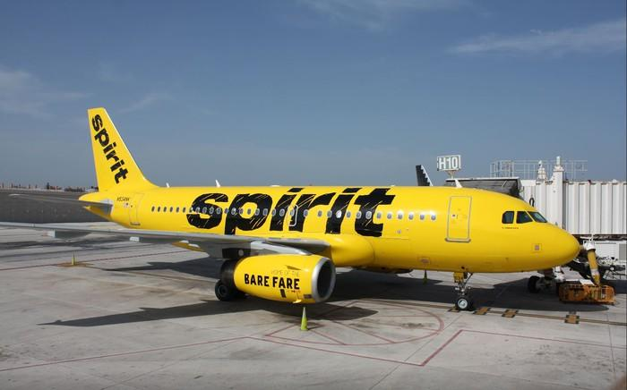 A yellow Spirit Airlines jet parked at an airport gate.