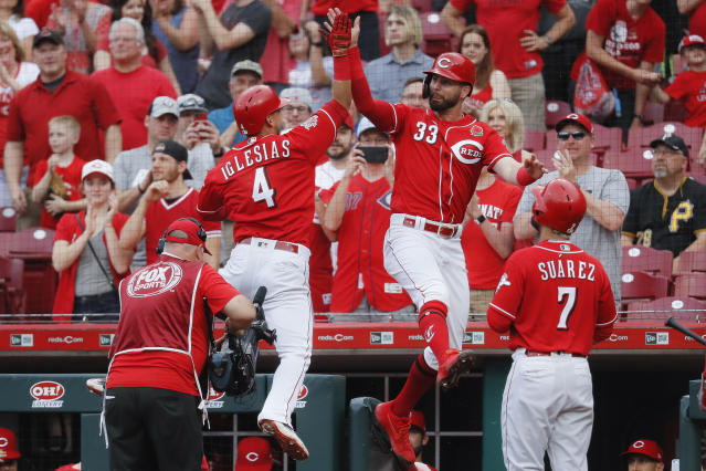 CORRECTS CITY TO CINCINNATI NOT COLUMBUS - Cincinnati Reds' Jose Iglesias (4) celebrates with Jesse Winker (33) after hitting a grand slam off Pittsburgh Pirates starting pitcher Mitch Keller in the first inning during the second baseball game of a doubleheader, Monday, May 27, 2019, in Cincinnati. (AP Photo/John Minchillo)