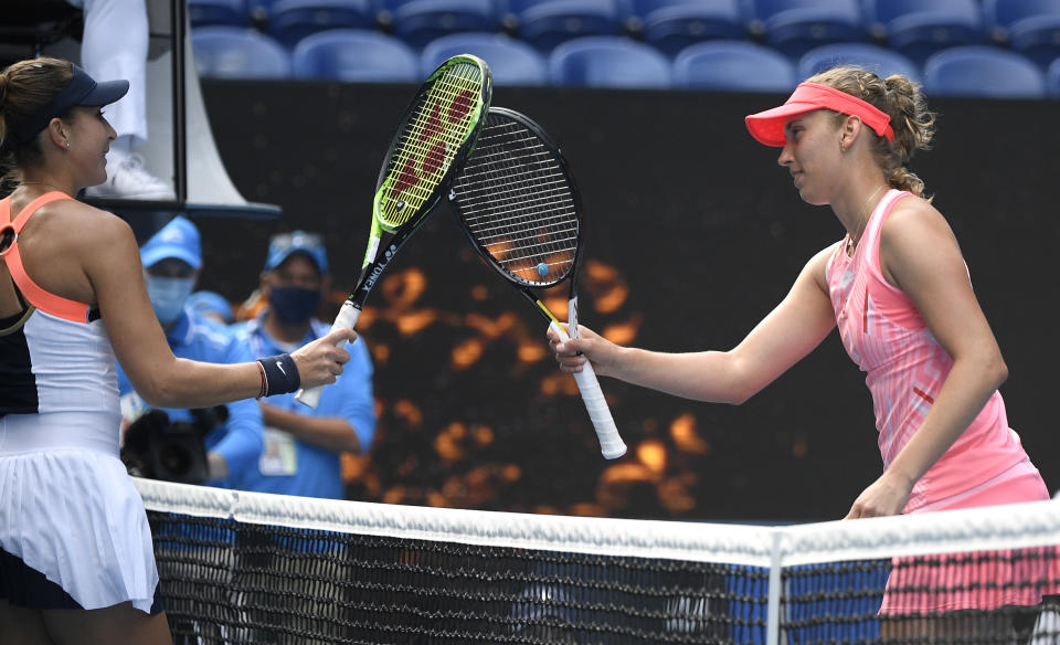Belgium's Elise Mertens, right, is congratulated by Switzerland's Belinda Bencic after winning their third round match at the Australian Open tennis championship in Melbourne, Australia, Saturday, Feb. 13, 2021.(AP Photo/Andy Brownbill)