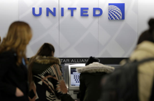 FILE- In this March 15, 2017, photo, people stand in line at a United Airlines counter at LaGuardia Airport in New York. A dog died on a United Airlines plane after a flight attendant ordered its owner to put the animal in the plane's overhead bin. United said Tuesday, March 13, 2018, that it took full responsibility for the incident on the Monday night flight from Houston to New York. (AP Photo/Seth Wenig, File)