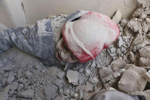 <p>A child is partly buried in rubble after airstrikes hit a rebel-held suburb near Damascus, Syria, Monday, Feb. 5, 2018. (Photo: Syrian Civil Defense White Helmets via AP) </p>