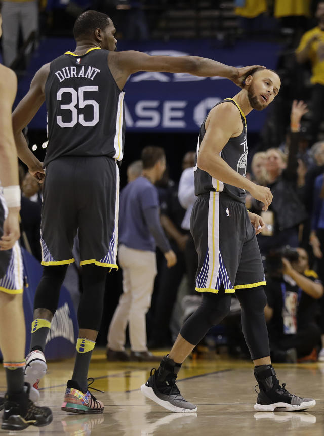 Golden State Warriors guard Stephen Curry, right, celebrates with forward Kevin Durant (35) during the second half of Game 4 of the NBA basketball Western Conference Finals against the Houston Rockets in Oakland, Calif., Tuesday, May 22, 2018. (AP Photo/Marcio Jose Sanchez)