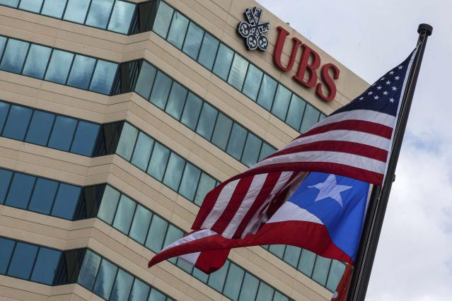 The national flags of Puerto Rico and the U.S. wave in front of a building belonging to UBS bank, whose retail customers' portfolios are heavily invested in Puerto Rico bonds, in the Hato Rey Financial District in San Juan, in this February 27, 2014 file photo. U.S. authorities are probing UBS AG for criminal fraud after a former broker in Puerto Rico allegedly directed clients to improperly borrow money to buy mutual funds that later plunged, according to lawyers representing some of the investors. REUTERS/Ana Martinez/Files (PUERTO RICO – Tags: BUSINESS POLITICS)