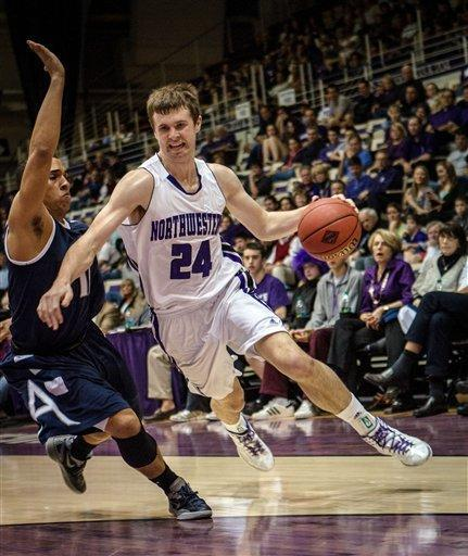 Northwestern's John Shurna drives past Akron's Alex Abreu during a first-round college basketball game in the NIT, in Evanston, Ill., on Tuesday, March 13, 2012. Northwestern won 76-74. (AP Photo/Charles Cherney)