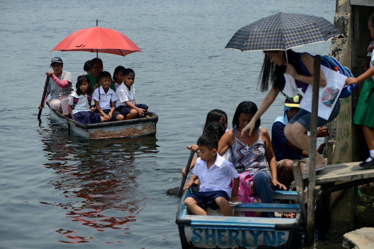 Filipino elementary school students ride on boats to go to Panghulo Elementary School near the Artex Compound in Malabon City in the Philippines on June 5, 2013.