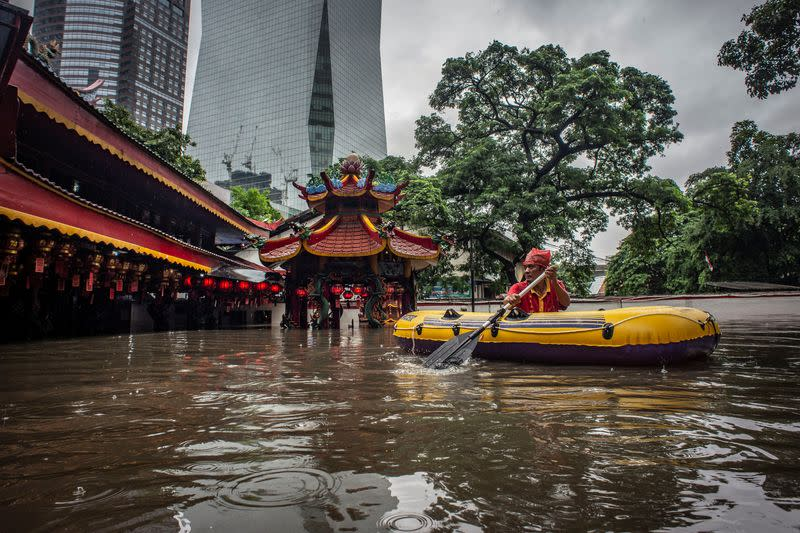 An elderly man uses an inflatable boat after floods hit his monastery in Jakarta