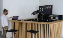An employee taps a display to order a coffee at the Barney Barista Bar in Zurich