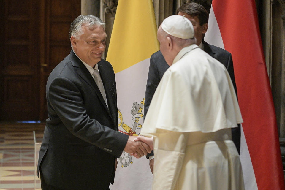 Pope Francis shakes hands with Hungarian Prime Minister Viktor Orban at Budapest's Museum of Fine Arts, Sunday, Sept. 12, 2021. Francis is opening his first foreign trip since undergoing major intestinal surgery in July, embarking on an intense, four-day, two-nation trip to Hungary and Slovakia that he has admitted might be overdoing it. (Vatican Media via AP)