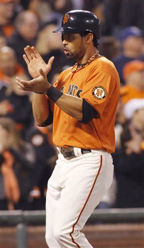 San Francisco Giants' Angel Pagan claps his hands as he scores on a Pablo Sandoval double against the Atlanta Braves during the third inning of a baseball game in San Francisco, Friday, Aug. 24, 2012. The Giants beat the Braves 5-3. (AP Photo/George Nikitin)