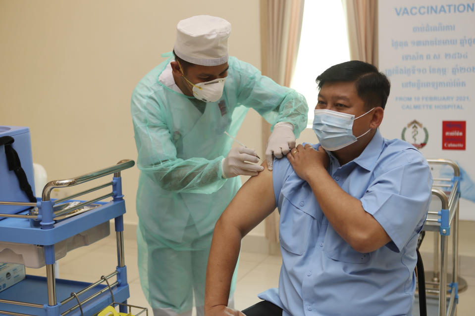 Cambodian Environment Minister Say Sam Al, right, receives a shot of the COVID-19 vaccine at Calmette hospital in Phnom Penh, Cambodia, Wednesday, Feb. 10, 2021. Cambodia began its inoculation campaign against the COVID-19 virus with vaccines donated from China, the country's closest ally. (AP Photo/Heng Sinith)