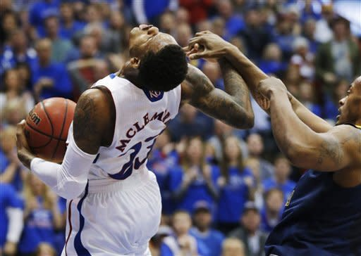 West Virginia forward Dominique Rutledge fouls Kansas guard Ben McLemore, left, during the first half of an NCAA college basketball game in Lawrence, Kan., Saturday, March 2, 2013. (AP Photo/Orlin Wagner)