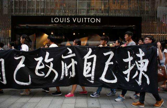 """Protesters carry a banner which reads """"We choose our own government"""" during a march at the financial Central district in Hong Kong September 24, 2014."""
