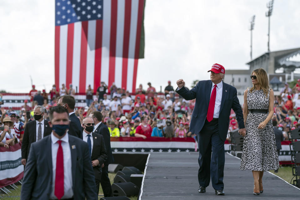 President Donald Trump walks with first lady Melania Trump after a campaign rally outside Raymond James Stadium, Thursday, Oct. 29, 2020, in Tampa. (AP Photo/Evan Vucci)