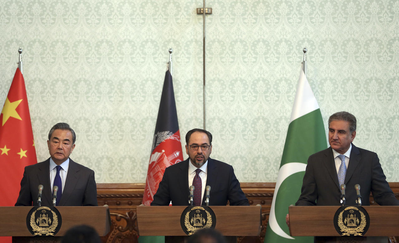 Afghanistan's Minister of Foreign Affairs Salahuddin Rabbani, center, speaks as Pakistan's Foreign Minister Shah Mehmood Qureshi, first right, and Chinese Foreign Minister Wang Yi, first left, listen during a joint press conference at the presidential palace in Kabul, Afghanistan, Saturday, Dec. 15, 2018. Afghanistan, Pakistan, and China are meeting in the Afghan capital to discuss trade, development and ending the region's relentless conflicts. (AP Photo/Massoud Hossaini)