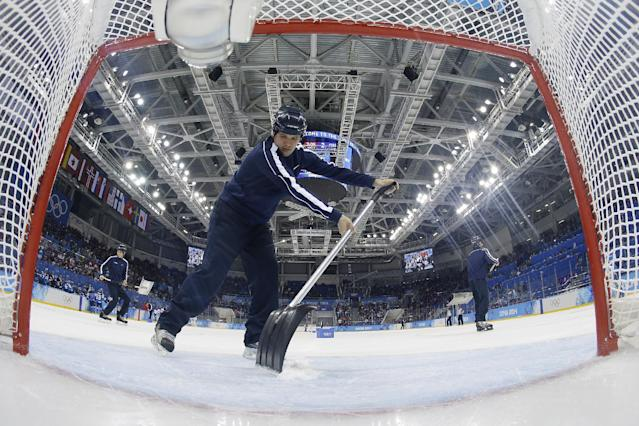 Volunteers refresh the ice during a break in the action in the game between Switzerland and Finland during the 2014 Winter Olympics women's ice hockey game at Shayba Arena, Wednesday, Feb. 12, 2014, in Sochi, Russia. (AP Photo/Matt Slocum, Pool)