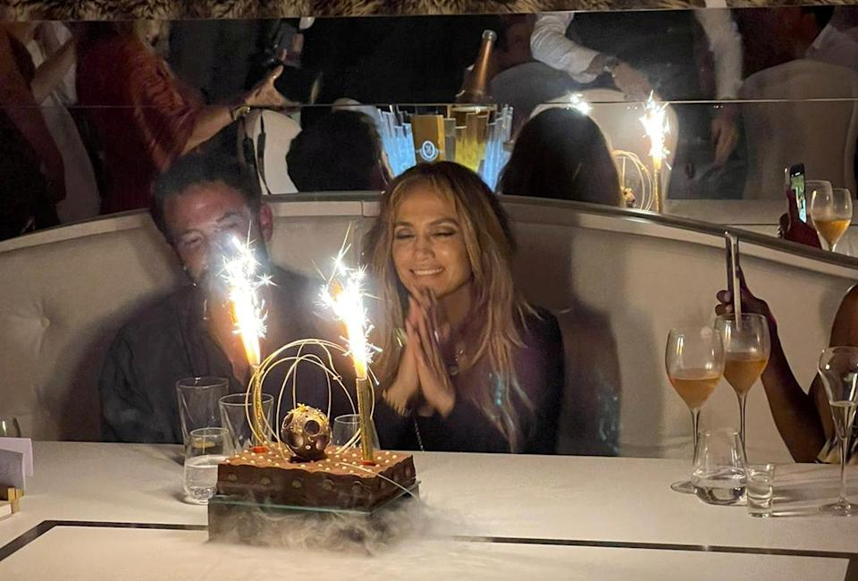 Lopez and Affleck were snuggled together in front of a cake adorned with sparklers (SWNS)