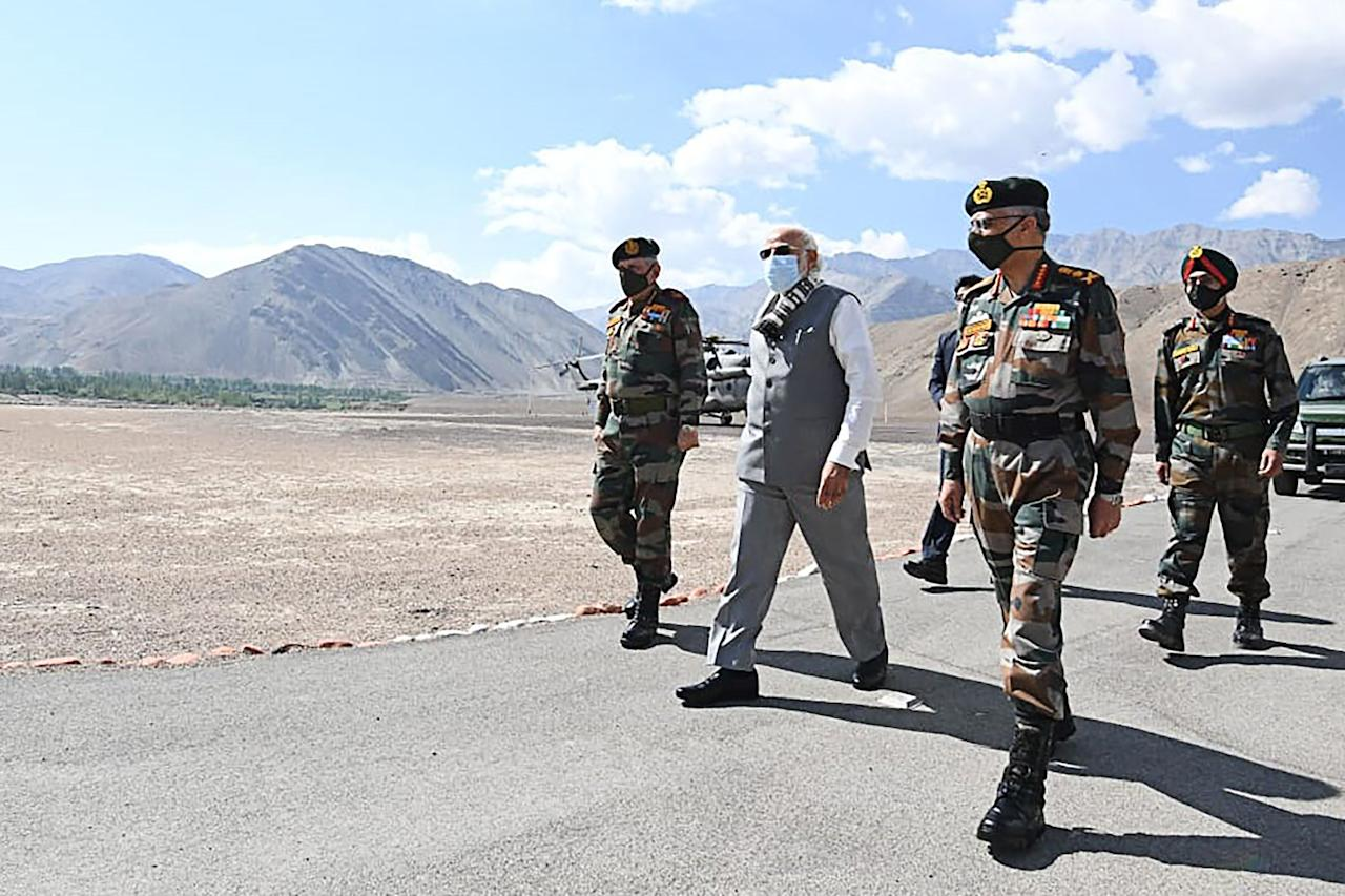 In this handout photograph taken on July 3, 2020 and released by the Indian Press Information Bureau (PIB), India's Prime Minister Narendra Modi (C) walks with military commanders as he arrives in Leh, the joint capital of the union territory of Ladakh. - Prime Minister Narendra Modi made a surprise visit to India's northern frontier region with China on July 3 in his first trip to the area since a deadly border clash last month. (Photo by Handout / PIB / AFP)
