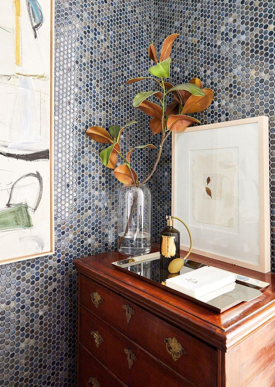 """<p>This small but mighty <a href=""""https://www.elledecor.com/design-decorate/house-interiors/a35386270/augusta-hoffman-east-village-apartment/"""" rel=""""nofollow noopener"""" target=""""_blank"""" data-ylk=""""slk:powder room"""" class=""""link rapid-noclick-resp"""">powder room</a> shows a vintage dresser topped with a framed artwork of tiny leaves and a single magnolia branch. </p>"""