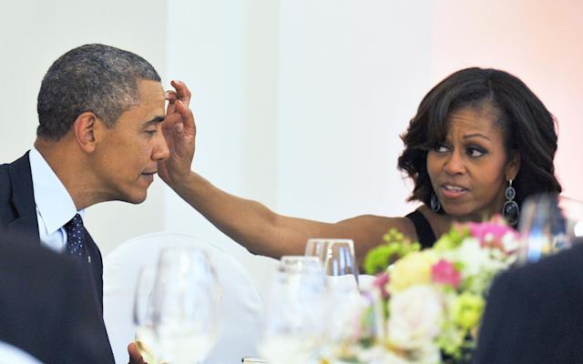 First lady Michelle Obama wipes something from President Obama's forehead during a dinner at the Schloss Charlottenburg Palace in Berlin, Germany on June 19, 2013.