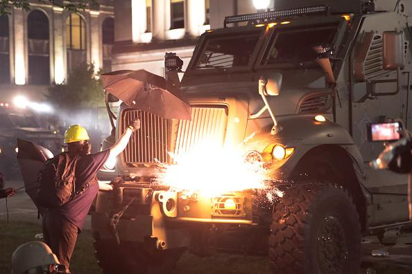 An explosive device detonates on the front of an armoured vehicle as protesters confront police in front of the Kenosha County Courthouse during a third night of unrest in Kenosha, Wisconsin.