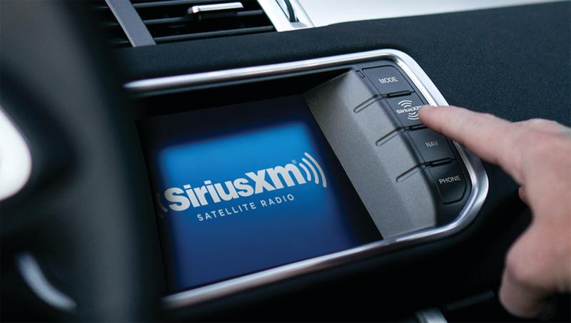 A driver pressing a button on their Sirius XM in-car radio display.