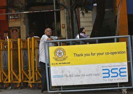 A man looks at a screen across the road displaying the Sensex on the facade of the Bombay Stock Exchange building in Mumbai