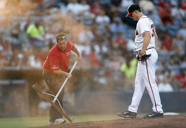 Atlanta Braves starting pitcher Gavin Floyd (32) looks on as a grounds crew member works to repair the mound in the second inning of a baseball game against the St. Louis Cardinals, Tuesday, May 6, 2014, in Atlanta. (AP Photo/John Bazemore)