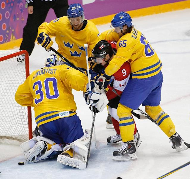 Alexander Edler (23), Erik Karlsson (65) and goalkeeper Henrik Lundqvist of Sweden (30) surround Matt Duchene of Canada (9) in front of Sweden's goal during the second period of the men's gold medal ice hockey game at the 2014 Winter Olympics, Sunday, Feb. 23, 2014, in Sochi, Russia. (AP Photo/Petr David Josek)