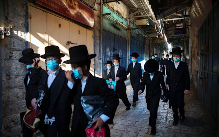 A group of Orthodox Jewish youth wear protective face masks as they walk in Jerusalem's Old City - AP