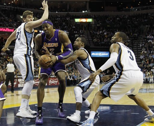 Los Angeles Lakers center Dwight Howard (12) goes to the basket against Memphis Grizzlies center Marc Gasol (33), of Spain, guard Mike Conley (11) and guard Wayne Ellington (3) in the first half of an NBA basketball game on Friday, Nov. 23, 2012, in Memphis, Tenn. (AP Photo/Lance Murphey)