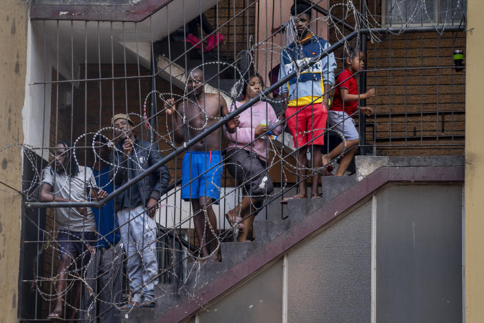 Residents of the densely populated Hillbrow neighborhood of downtown Johannesburg, confined in an attempt to prevent the spread coronavirus, stand on a staircase, Friday, March 27, 2020. South Africa went into a nationwide lockdown for 21 days in an effort to mitigate the spread to the coronavirus. The new coronavirus causes mild or moderate symptoms for most people, but for some, especially older adults and people with existing health problems, it can cause more severe illness or death. (AP Photo/Jerome Delay)