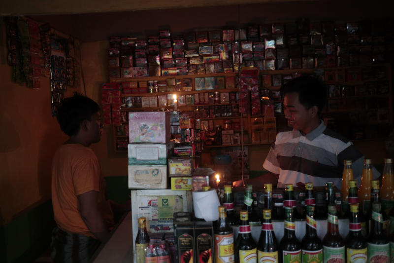 A vendor lights candles at his herbal drink stall during a power outage in Jakarta, Indonesia, Sunday, Aug. 4, 2019. Indonesia's sprawling capital and other parts of Java island have been hit by a massive power outage affecting millions of people. (AP Photo/Dita Alangkara)