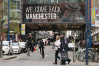FILE - In this Monday, April 12, 2021 file photo, shoppers in central Manchester, England, as coronavirus restrictions are eased in England. Thanks to an efficient vaccine roll out program and high uptake rates, Britain is finally saying goodbye to months of tough lockdown restrictions. From Monday May 17, 2021, all restaurants and bars can fully reopen, as can hotels, cinemas, theatres and museums, and for the first time since March 2020, Britons can hug friends and family and meet up inside other people's houses. (AP Photo/Jon Super, File)