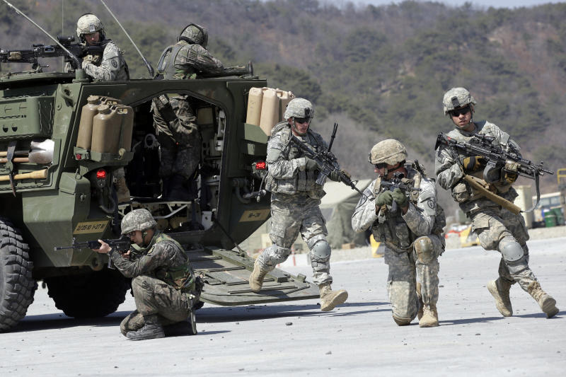 FILE - In this March 25, 2015, file photo, U.S. Army soldiers from the 25th Infantry Division's 2nd Stryker Brigade Combat Team and South Korean soldiers take their positions during a demonstration of the combined arms live-fire exercise as part of the annual joint military exercise between South Korea and the United States at the Rodriquez Multi-Purpose Range Complex in Pocheon, north of Seoul, South Korea. The South Korean and U.S. militaries have postponed on Thursday, Feb. 27, 2020, their annual joint drills out of concerns over a virus outbreak. (AP Photo/Lee Jin-man, File)